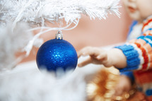 toddler reaching for blue ornament on a white Christmas tree
