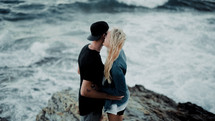 a couple kissing on a rocky shore