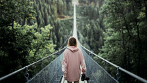 a woman with a camera crossing a swinging bridge