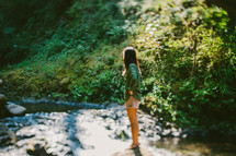 woman standing next to a stream