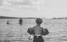 a child in a floatie playing at a lake