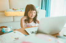 Little Asian girl with laptop computer or notebook in living rome at home
