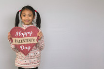 A child holding a Happy Valentine's day sign