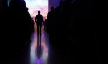a man walking down an aisle during a worship service