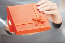 a woman opening a red gift box