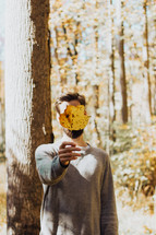 a man holding up a fall leaf in front of his face
