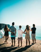 friends standing on cliffs overlooking a beach