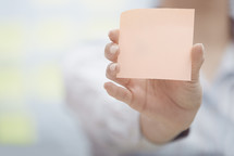 a woman holding a pad of blank sticky notes