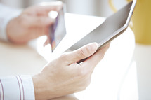 a person holding a tablet and credit card
