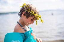 a child in a floatie playing at a lake with a crown of leaves