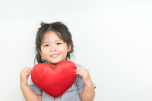 toddler girl holding a red heart