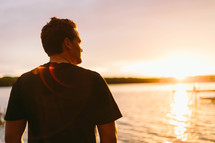 man standing at a shore at sunset