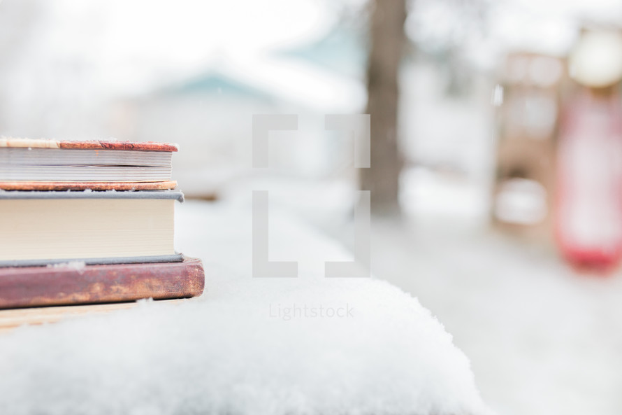 a stack of books on a table in the snow