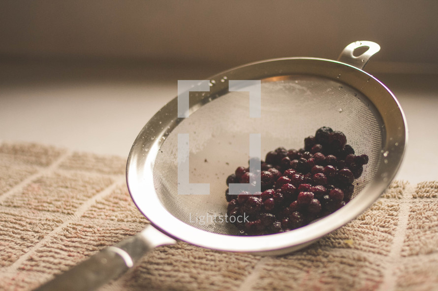 Cranberries in a strainer.