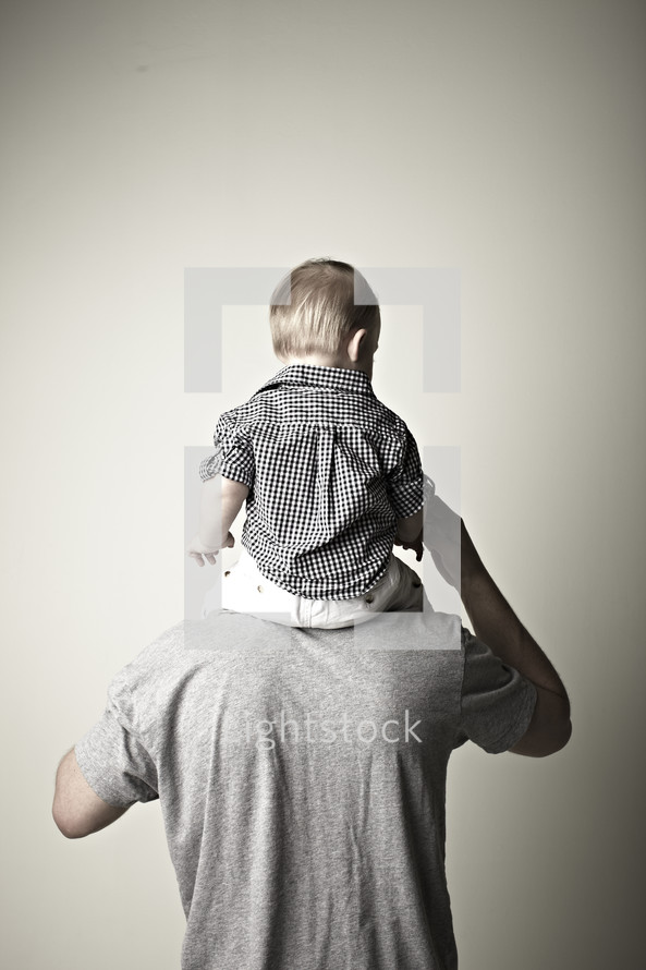 A boy sitting on his Dad's shoulders