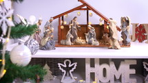 Jesus Christ Nativity scene near Christmas tree. Jesus Christ birth in a stable with Mary and Joseph figures. Christmas scene. Dolly shot