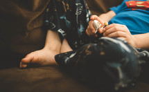 Child sitting on the couch holding toys.