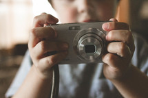 Child holding a digital camera.