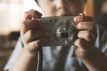 Child holding a digital camera.