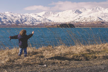 A child with arms outstretched stands before  a lake and a snow covered mountain range.