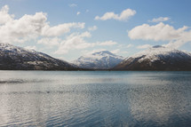 Clouds covering snowy mountains near water.