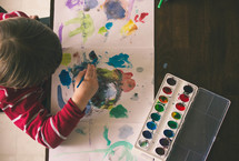 a boy child painting with watercolors