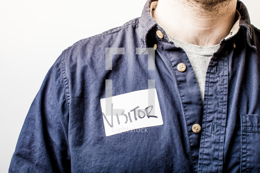 Man in a denim shirt with a visitor's tag.