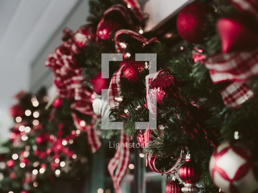 Christmas garland with red and white ribbon and ornaments.