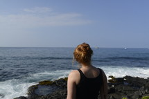 a woman standing on a rocky shore looking out over the ocean