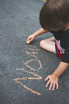 boy child writing his name with sidewalk chalk