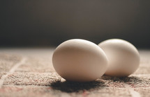 Two eggs on a tile countertop.