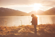 Silhouette of a boy in the sunlight near a lake surrounded by mountains.