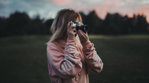 a woman with a camera taking a picture at sunset
