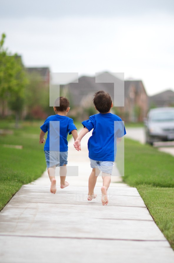Two little boys running down a sidewalk