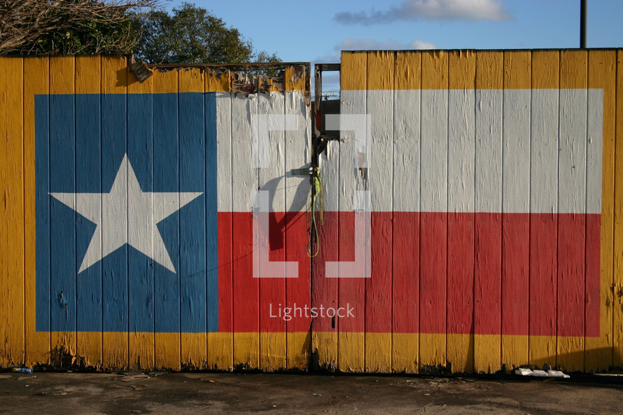 A Texas flag painted on a yellow fence