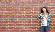 a girl standing in front of a brick wall