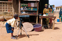 Young African boy starring through a telescopic camera in a market