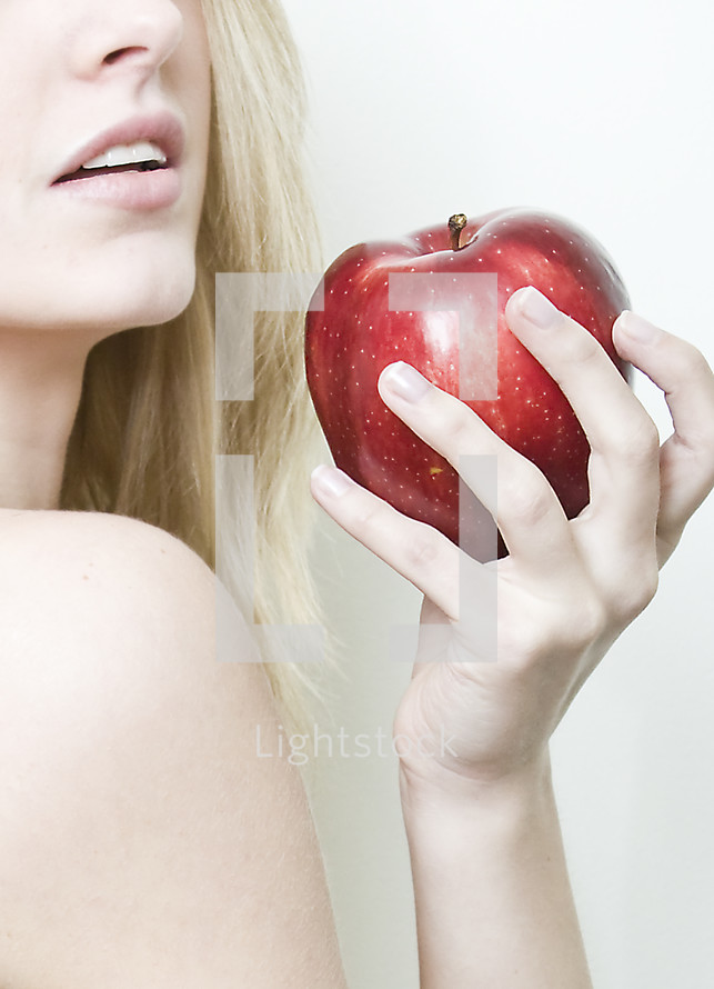 Woman (Eve) holding a red apple near her face.