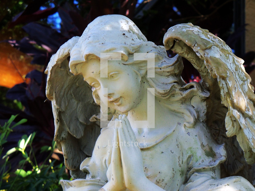 A statue of a praying female angel figure with a smiling face and prayerful pose adorns a courtyard in a church cemetery.