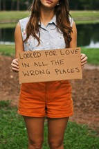 woman holding sign with the words LOOKED FOR LOVE IN ALL THE WRONG PLACES