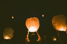 realeasing paper lanterns into the night sky