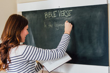 A woman writing a Bible verse on a chalkboard