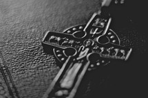 A cross medallion sitting on a Bible