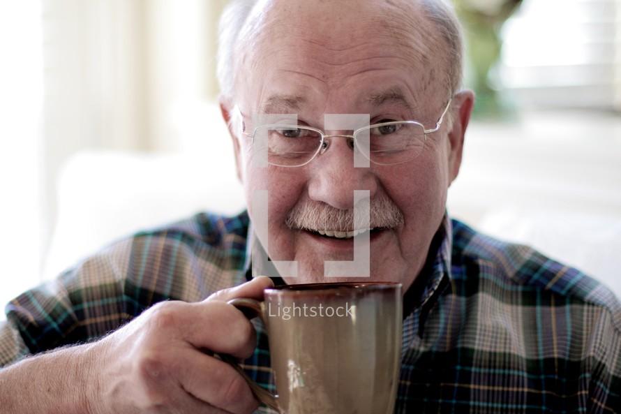 Elderly man drinking cup of coffee