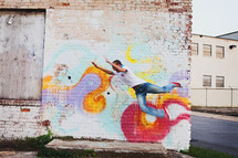 man jumping in front of a painted brick wall