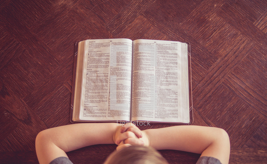 boy child with praying hands beside a Bible