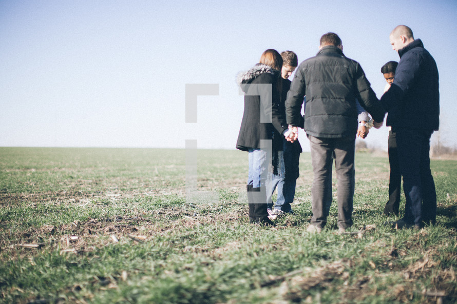 group of people holding hands in prayer in a field