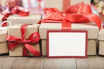 brown gift boxes with red ribbons and a blank gift tag