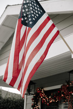 An American flag hanging above a front porch decorated for Christmas.
