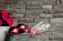 An arrangement of Christmas decorations against a backdrop of a gray brick wall.